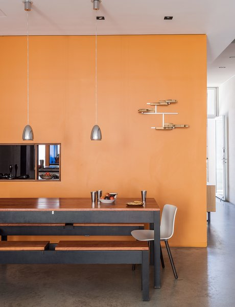 Sheetrock surfaces comprise many of the interior walls, including one situated between the kitchen and dining area, which is furnished by benches and a table designed and built by Baumann, alongside HAL chairs by Jasper Morrison for Vitra.