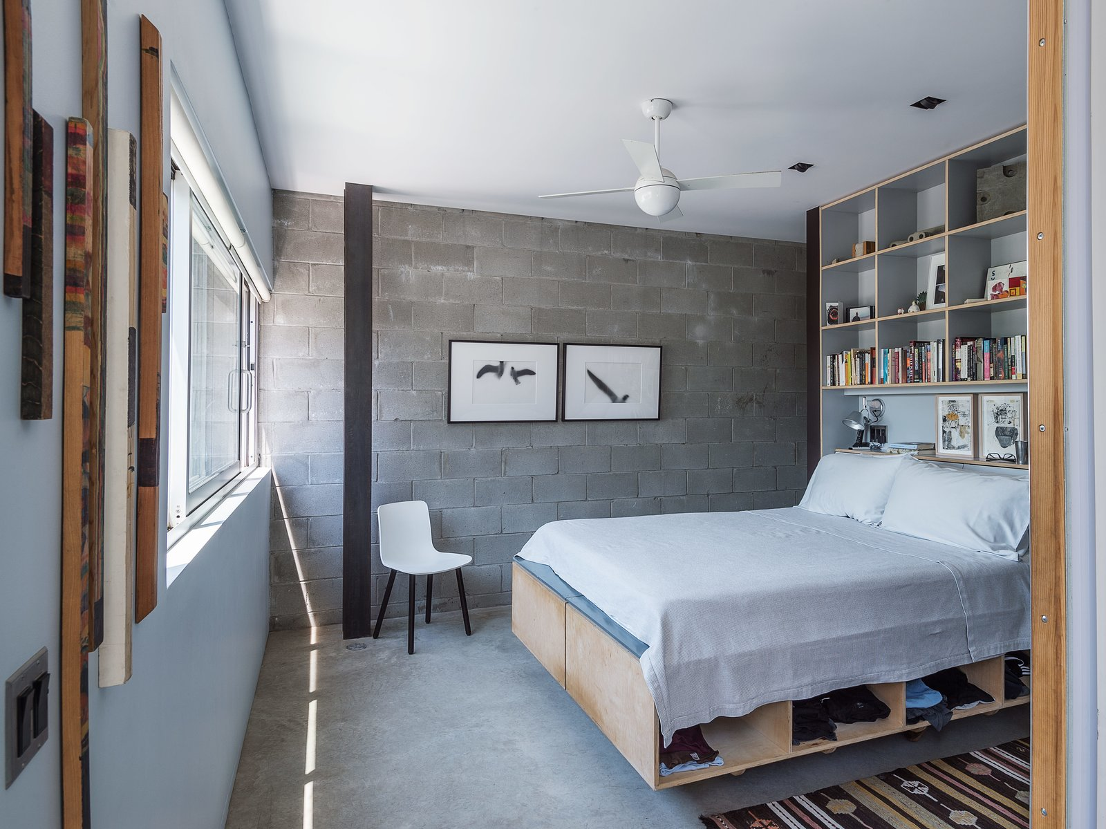 Baumann designed the plywood bed frame and shelving unit in the master bedroom, adjacent to an exposed cinder-block wall, a new addition to the structure.  Tagged: Bedroom, Bed, Chair, Ceiling Lighting, and Concrete Floor. Bedroom by wx