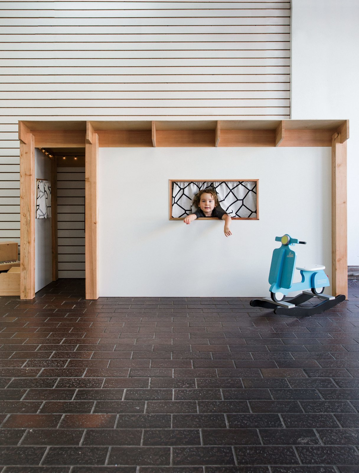 """Children streaming in for a workshop are greeted by an Eichler-inspired playhouse (dubbed the """"Tikeler"""") designed and built by The Butterfly Joint's founder, Danny Montoya. Tagged: Kids Room and Playroom.  Photo 1 of 1 in In a San Francisco Workshop, Kids Take on Carpentry with Mini Chisels and Saws"""