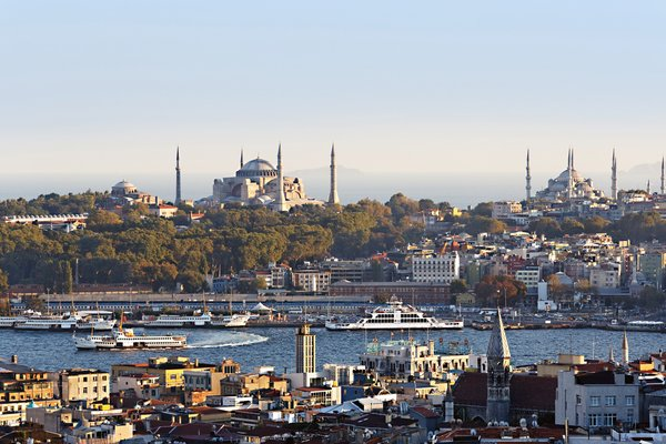 """Looking at Istanbul's old city from the trendy neighborhood of Beyoğlu, one can see the Hagia Sophia at left (rebuilt for the last time in the 6th century) and the 17th-century Sultanahmet (or """"Blue"""") Mosque with its six minarets at right."""