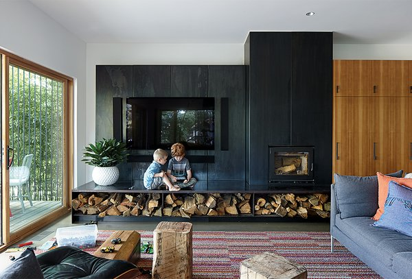"""Hufft Projects designed the blackened steel """"fireplace wall,"""" which includes a Lennox wood-burning stove and an entertainment center. The Vela sofa is by Room & Board, and the rug is composed of carpet tiles from FLOR."""