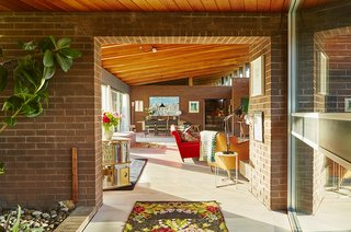 Quirky 1970s House in the English Countryside Showcases an Amazing Modern Furniture Collection - Photo 1 of 18 - Sheridan Coakley, owner of the London-based furnishings purveyor SCP, uses his circa-1970s home as a testing ground for the furnishings he carries in his company's inventory. In the foreground, a Balzac lounge chair by Matthew Hilton is draped with a Donna Wilson blanket.