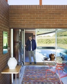 Quirky 1970s House in the English Countryside Showcases an Amazing Modern Furniture Collection - Photo 2 of 18 - Coakley commutes an hour into London, where his two SCP stores are located. In the entryway, a pair of Jasper Morrison tables join a vintage Moroccan rug. The circa 1980s Thinking Man's Chair, also by Morrison, is in the foreground.
