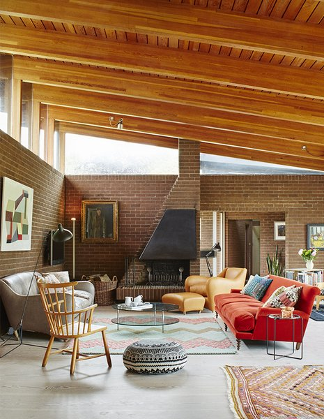 In the open-plan living and dining room, a dramatically sloped roofline allows for generous clerestory windows.