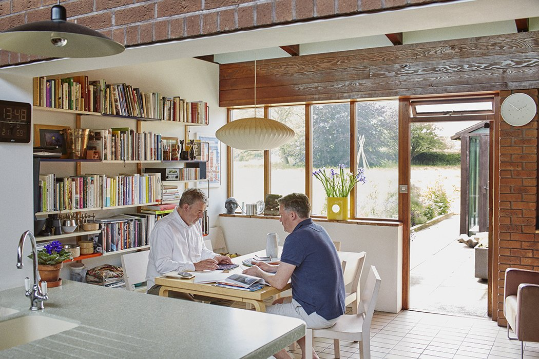 In the eat-in portion of the kitchen, a George Nelson Bubble Lamp hangs above an Artek table and chairs by Alvar Aalto. Tagged: Dining Room, Table, Chair, and Pendant Lighting.  Photo 7 of 18 in Quirky 1970s House in the English Countryside Showcases an Amazing Modern Furniture Collection
