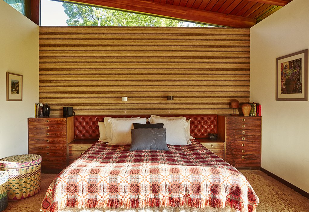 The master bedroom boasts a 1970s tufted headboard from Heals Leather and a wall covering of burlap, wool and silk by David Hicks. The bed covering is vintage, 1950s, and the Blocks linen basket was designed by Donna Wilson and made by the People of the Sun, a nonprofit based in Malawi. Quirky 1970s House in the English Countryside Showcases an Amazing Modern Furniture Collection - Photo 13 of 18
