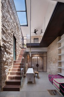 A 250-Year-Old Stone House in Israel With a Surprisingly Modern Interior - Photo 3 of 7 - Irit and Zohar imagined a space that would be a cohesive blend of old and new. Stone, metal, glass, and wood intersect in the interior courtyard. Large skylights bring light in, and play upon the indoor-outdoor functionality of the courtyard space.