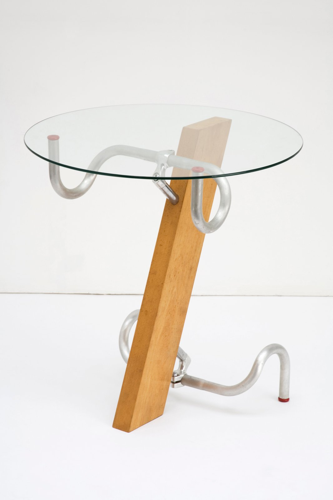 "Early in Jasper Morrison's career, he built a table of beech wood, glass, and two bicycle racing bar handles to give the piece a ""mass-produced quality"" without benefit of a manufacturer. In 1983, the materials for one table cost about £20.00, and he sold them for five times that. ""The somewhat eclectic shape of the table itself was fitting to the mood of the time and my own frame of mind, a kind of poetic, anti-establishment, business-like attitude,"" Morrison is reported as saying years later.  Design Museum London's Extraordinary Stories about Ordinary Things by Rebecca L. Weber"