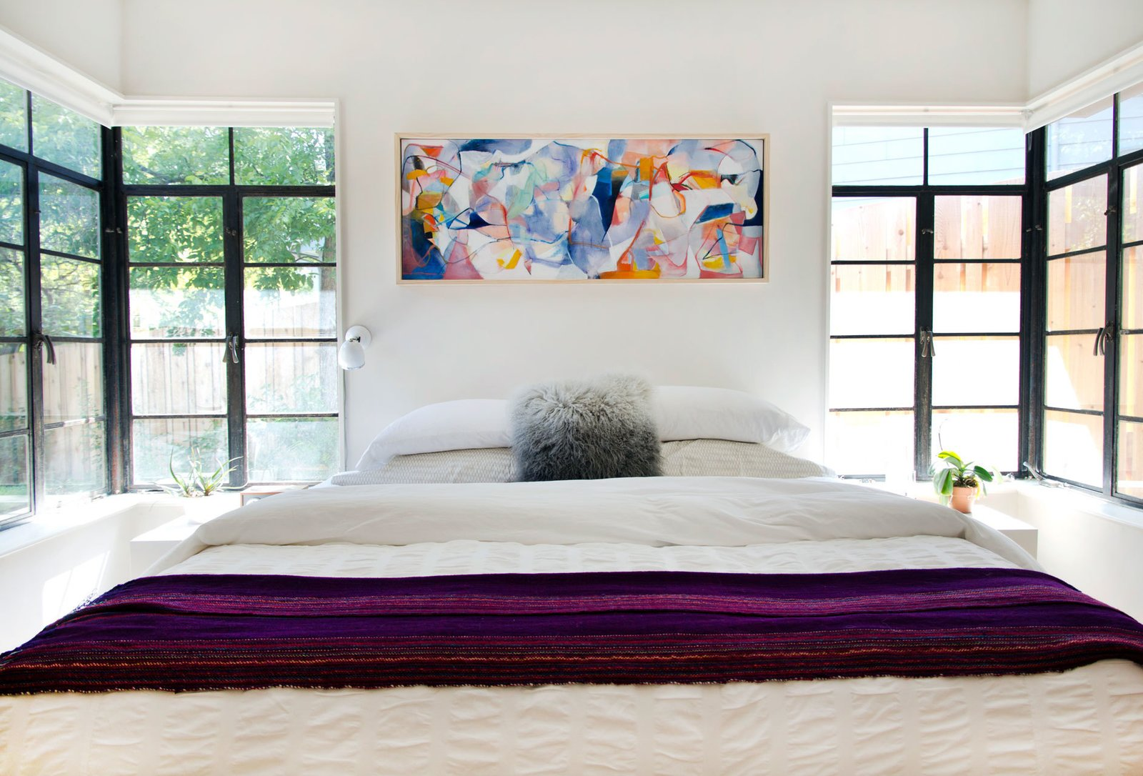 "The bedroom enjoys ample natural light, thanks to the windows on either side of the Charles Rogers bed. ""We centered all our bedroom doors around the central hallway skylight,"" says Allison. The painting is by Pat Diaz."