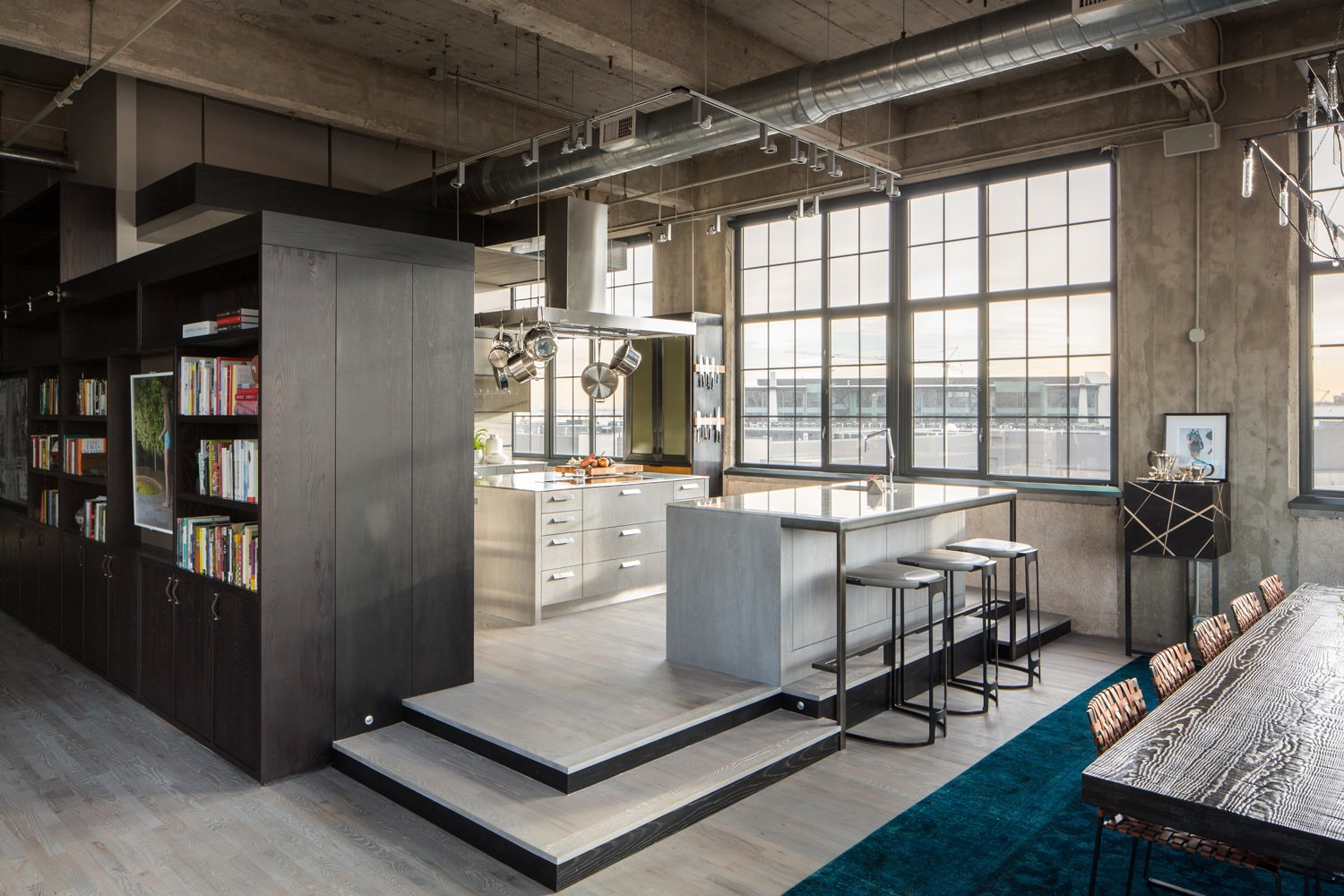 The 1920s building was converted into lofts in 2000. The client started out looking for new cabinet hardware and an improved connection between the laundry room and the guest bath, but ultimately decided to work with the firms on a full overhaul.  Modern Homes in Colorado by Luke Hopping from Industrial Loft in a Former Flour Mill