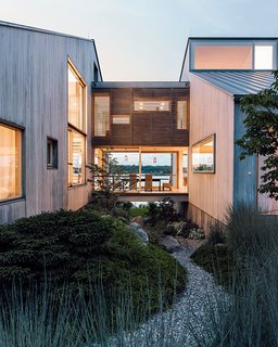Seaside Views Make This Vacation Home a Relaxing Retreat - Photo 1 of 12 - Gray Organschi took down a worn-out 1970s summer home and reinvented it as a serene pair of bleached cedar volumes connected by a glass bridge.