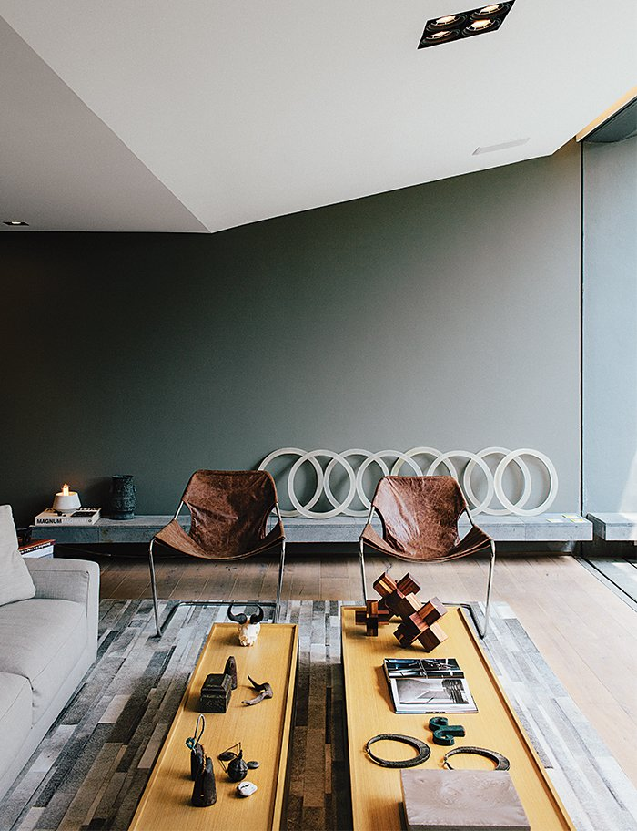 In the sitting area, two leather Paulistano chairs by Paulo Mendes da Rocha top a rug by Yerra; the wall paint is Comex. Tagged: Living Room, Chair, and Coffee Tables.  Photo 3 of 15 in A Lush Retreat With a Sheltered Rooftop Pool in Mexico City