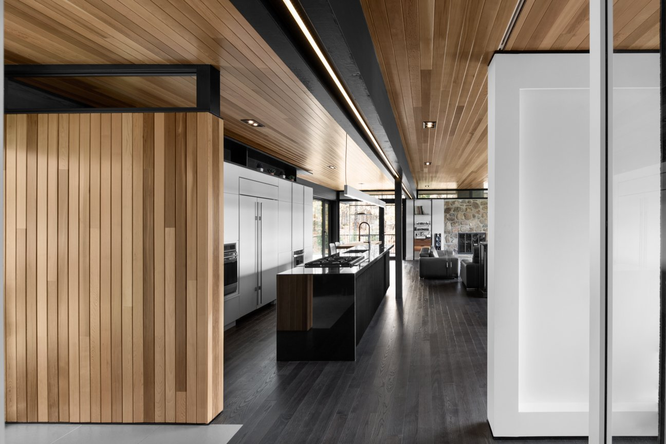 Cedar planks and gray-stained oak flooring line the interior. A minimalist LED lighting strip by Systemalux runs through the kitchen area, enhancing the wood ceiling's reddish tone.  Midcentury Homes by Dwell from The Phoenix