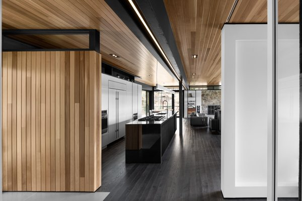 Cedar planks and gray-stained oak flooring line the interior. A minimalist LED lighting strip by Systemalux runs through the kitchen area, enhancing the wood ceiling's reddish tone. Photo 4 of The Phoenix modern home