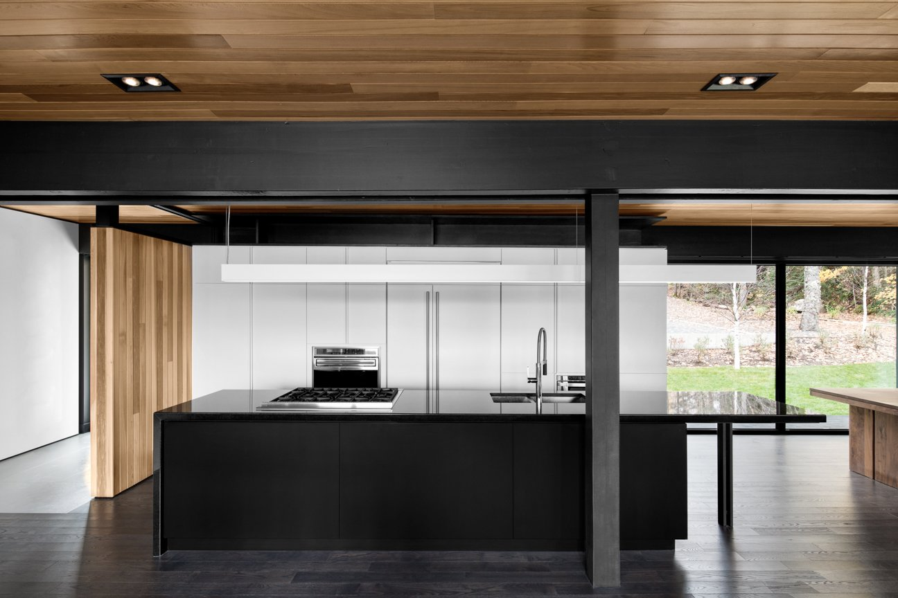 The kitchen's black countertops were cut from Nero Assoluto granite. The sink and faucet are from Quebec-based company Rubi. Appliances are from Wolf.  Kitchens by Kimball Hales from The Phoenix