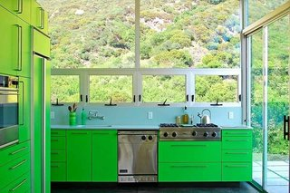 These 9 Spaces Show How to Rock a Monochromatic Color Scheme - Photo 4 of 9 - Taking cues from the outlying rolling landscape of this Malibu home, architect Bruce Bolander selected a bright green hue for the cabinets and refrigerator of this kitchen. The connection to nature is evident, thanks to the grand views through the windows above the sink and stovetop area.