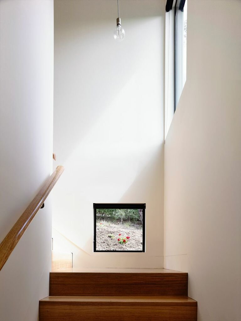 """""""I love this low-level stair window. It's at head height when you're at the bottom of the stairs; it gives you a glimpse of, and connection to, the garden outside. Most of the windows capture what I'd call 'hero shots,' but some, like this one, are completely unexpected.""""  Photo 6 of 8 in A Breezy Modern Beach House Sits Among the Trees in Australia"""