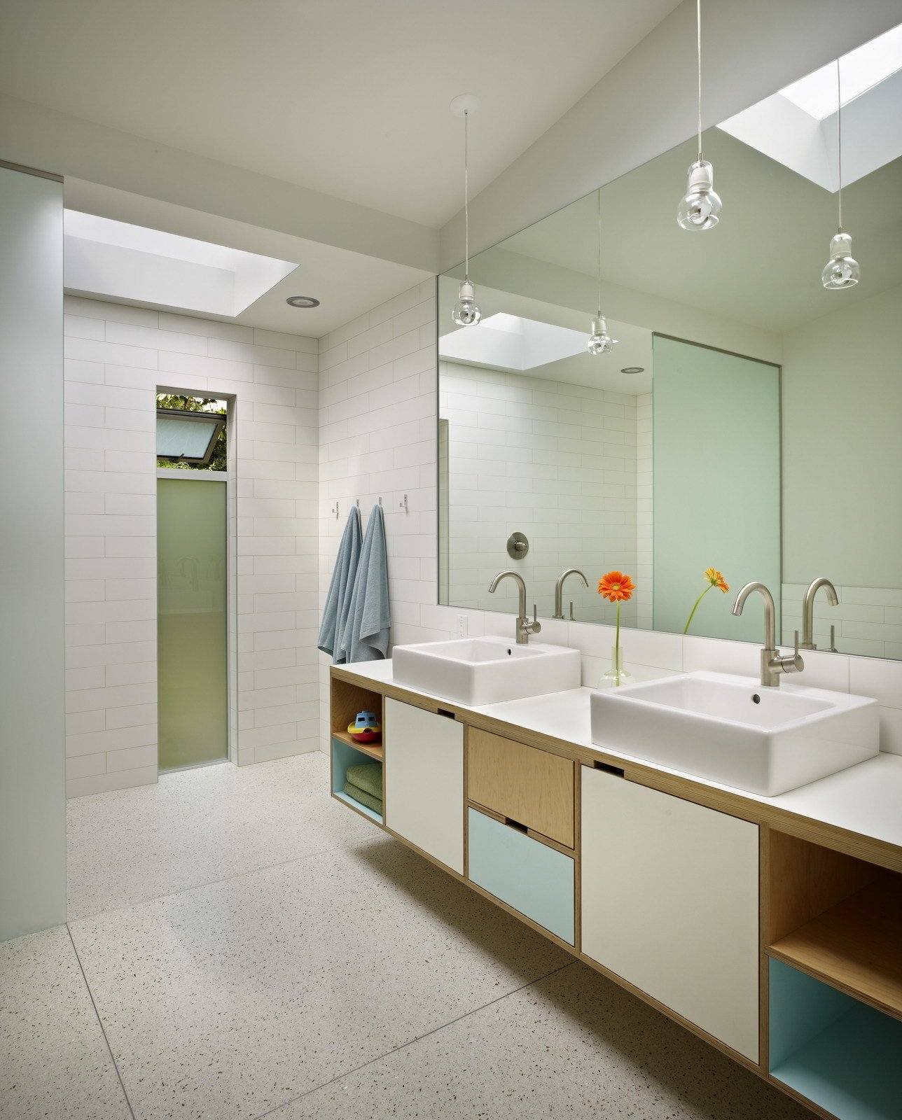In the kids' bathroom, a colorful custom vanity complements the clean, white palette. Mirrors extend up into a skylight to draw light in over the vanity.  Midcentury Homes by Dwell from A Mid-Century Renovation in Washington