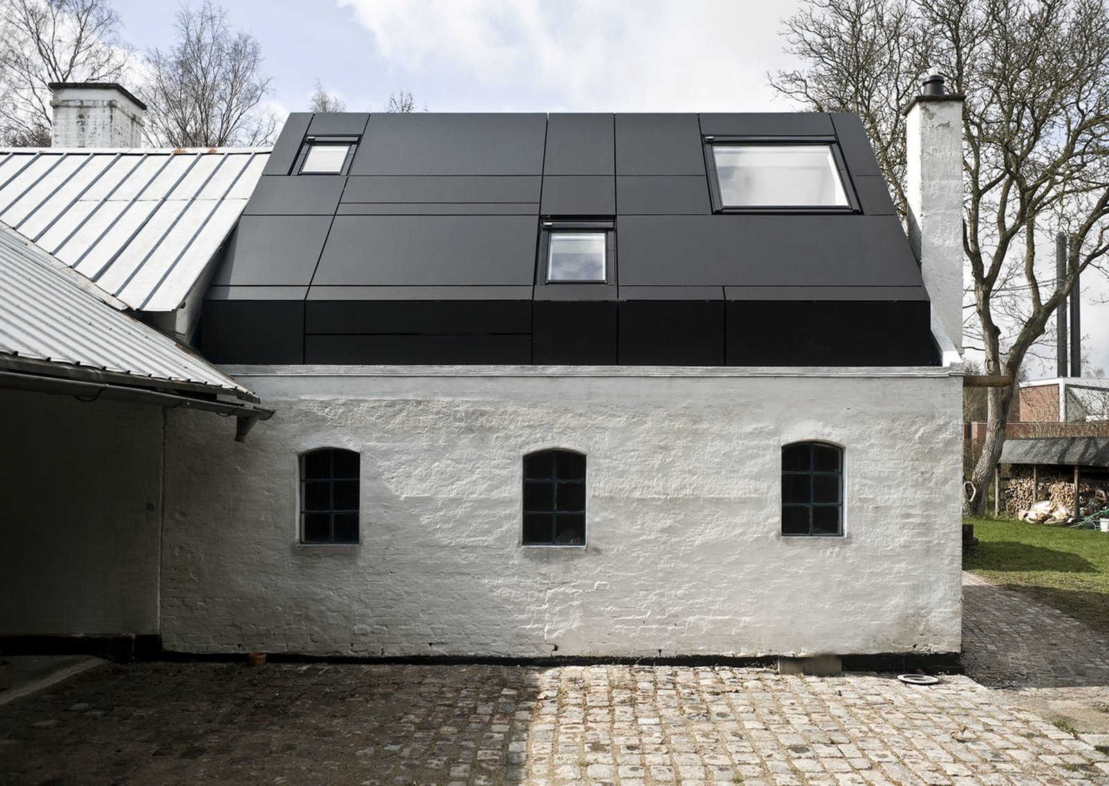 Although the old window and door openings of the original building remain visible from the exterior, they were covered on the inside with veneer. Instead, large windows on the roof and a clear glass door supply the interior with adequate daylight.  Photo 2 of 6 in Danish Farmhouse Turned Contemporary Art Studio