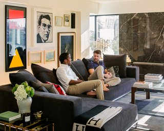 Byron Peart and partner Stefan Weisgerber lounge in their art-filled living room.