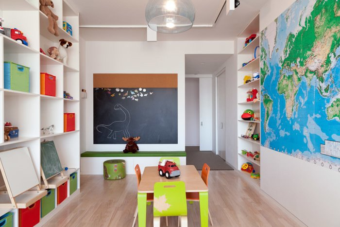 The kids' playroom features built-in storage and a Fly pendant from Design Within Reach. Reddy purchased the mural from World Maps Online and the small table and chairs from Igloo Play.  How to Design With Maps by Zachary Edelson from A Family-Friendly New York City Apartment