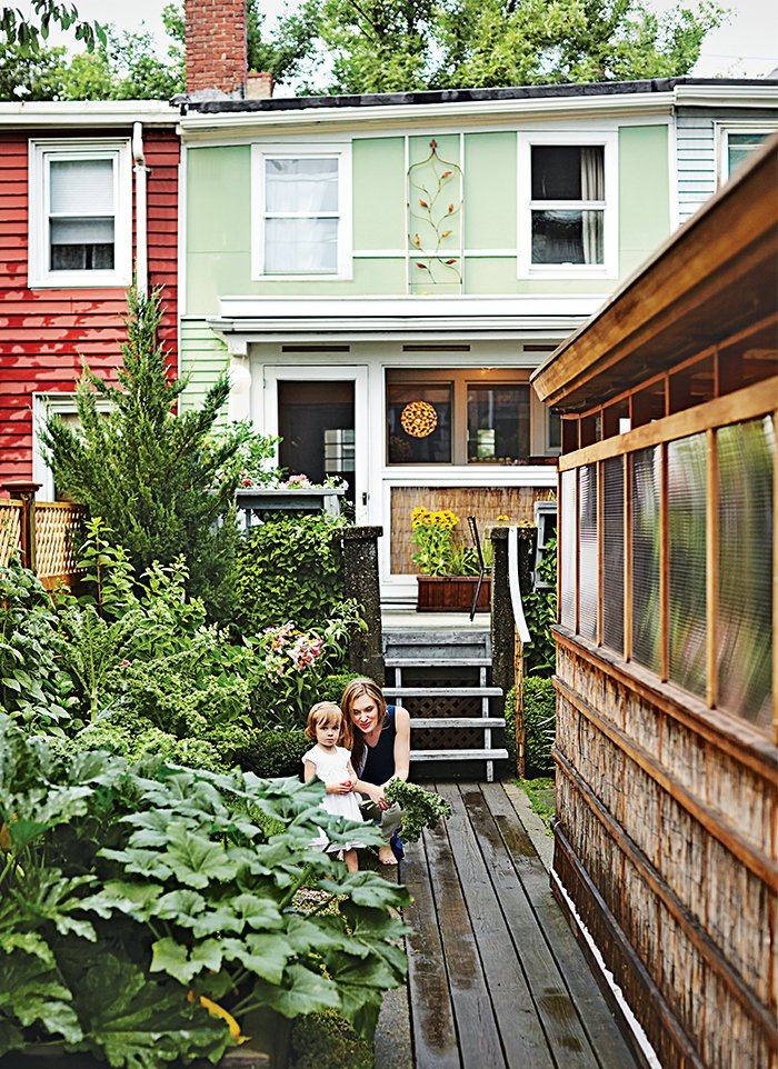 Lyle Bradley spent years of weekends and evenings resurrecting an East Boston structure using his carpentry skills, repurposed materials, and clever space-saving interventions. The revitalized 800-square-foot residence joins a rejuvenated backyard, where Bradley's wife, Kara Lashley, and their daughter, Lily, pose next to Bradley's new freestanding workshop.