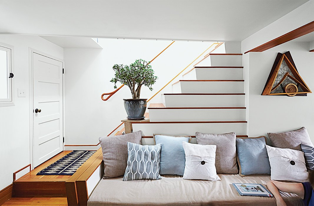 In the living room, the stair's lower step reaches out to form an arm, while the ascending stairs create a natural incline for cushions.  190+ Best Modern Staircase Ideas by Dwell from Run-Down Row House in Boston Becomes a Quiet Urban Escape with Two Green Roofs