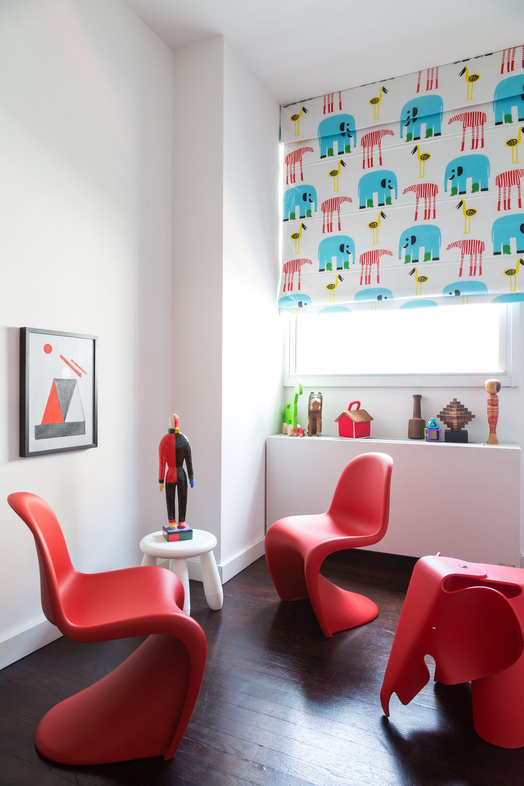 Panton chairs from Vitra adorn the guest bedroom and office. Tagged: Kids Room, Playroom, Chair, and Dark Hardwood Floor.  Lovely NYC Abodes That Will Give You Apartment Envy by Allie Weiss from Furnish by Color: Red