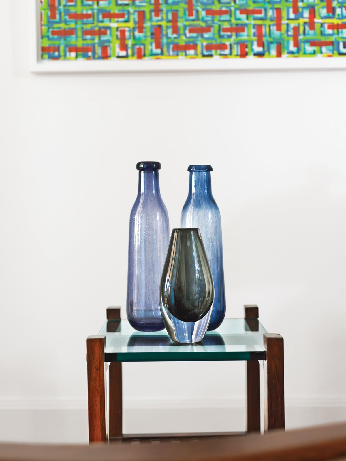 A trio of glass pieces by Gunnel Sahlin for Kosta Boda lays on top of a glass and wooden side table.  Photo 7 of 18 in A Neoclassical Gallery Home in Belgium