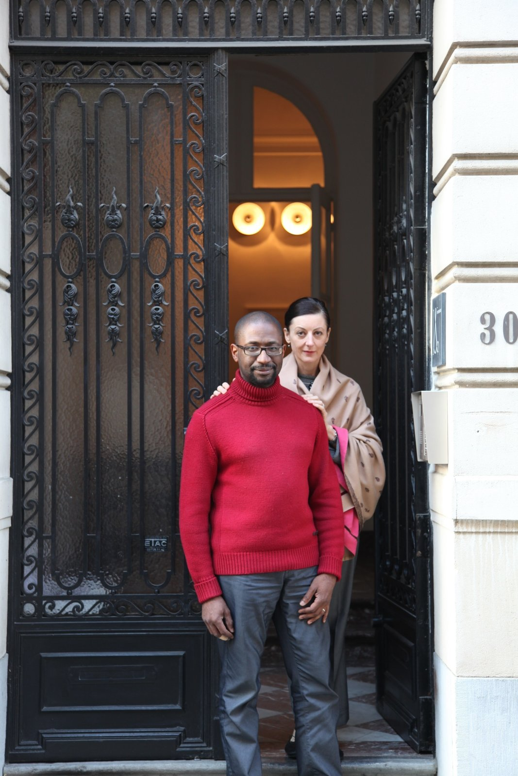 "Udechuku and Smith stand in front of their neoclassical townhouse in Brussels. They met at law school in Australia (Smith is Australian, Udechuku is British) and together discovered their love of design while furnishing their homes over the years—in Australia, in London, in San Francisco, and later in Luxembourg. Today, clients come to them ""for the breadth of our design knowledge, relentless pursuit of perfection for each client, and for our ability to research and source rare and unusual pieces,"" says Udechuku.  Photo 14 of 18 in A Neoclassical Gallery Home in Belgium"