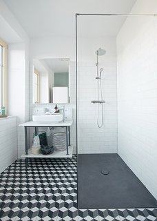 10 Best Modern Showers to Inspire Your Bathroom Renovation - Photo 2 of 10 - In renovating her home in Schönkirchen-Reyersdorf, Austria, Katharina Reckendorfer repurposed what she could—like a bathtub and vanity—and streamlined the rest. New black and white graphic cement tile from Mosaic del Sur, Hansgrohe fixtures, a shower plate from Bette, and Farrow & Ball's Chappell Green paint round out the room.