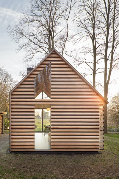 The house may appear conventional at a glance, but a closer look shows how Oostenbruggen has pushed the boundaries of the traditional gabled typology. It has an asymmetrical roof, with slate shingles that extend down the eastern side to close it off completely. Photo 2 of Utrecht Cabin modern home