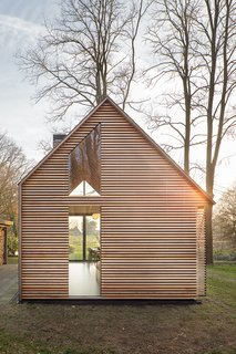 This Light-Filled Cabin in the Netherlands Is Completely Made by Hand - Photo 2 of 9 - The house may appear conventional at a glance, but a closer look shows how Oostenbruggen has pushed the boundaries of the traditional gabled typology. It has an asymmetrical roof, with slate shingles that extend down the eastern side to close it off completely.