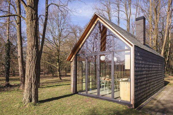 "With one side of the house closed off, views are directed through the glazed south and west facades to the grassy clearing beyond. ""We planted tens of thousands of blue bells and lots of rhododendrons,"" Oostenbruggen says of the green space. ""The setting developed over time."" Photo 3 of Utrecht Cabin modern home"