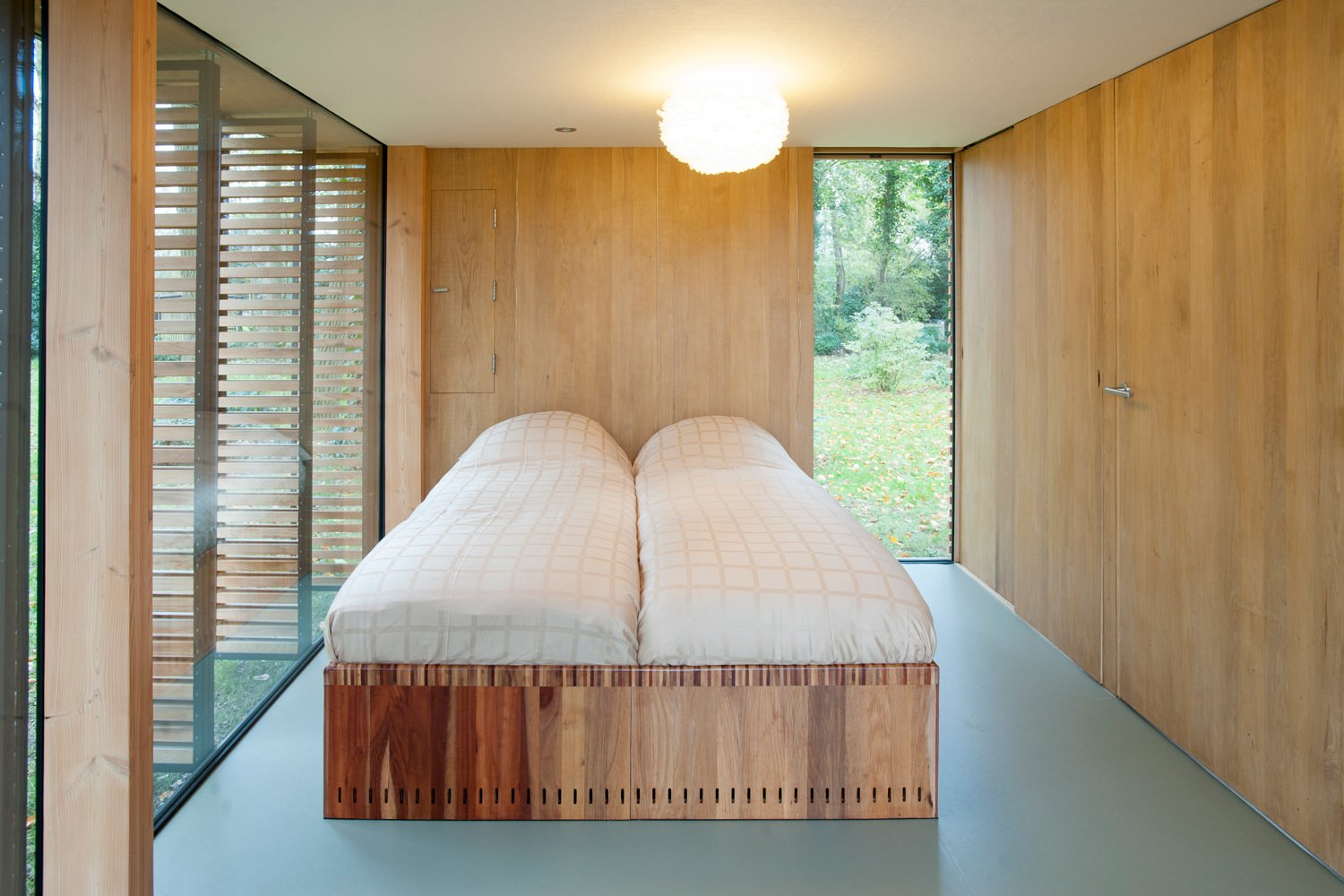 Light breaks through the bedroom's north wall through a vertical window that cuts from the floor up past the second floor mezzanine to the roof's ridgeline. The bed is custom. Tagged: Bedroom, Bed, and Ceiling Lighting.  Photo 5 of 9 in This Light-Filled Cabin in the Netherlands Is Completely Made by Hand from Utrecht Cabin