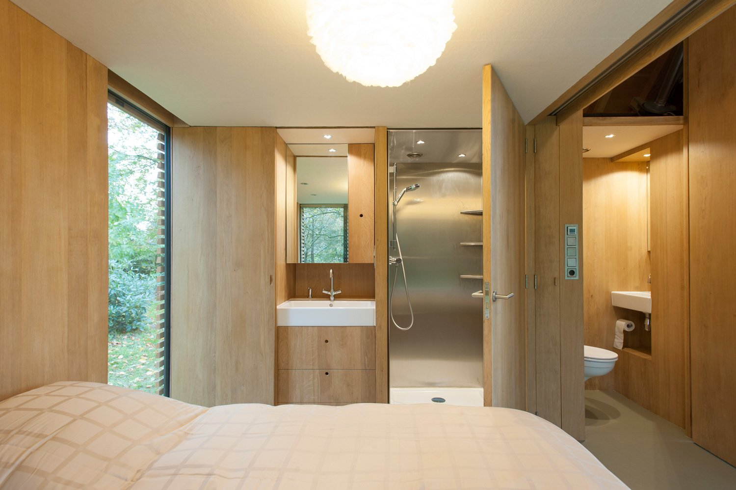 In the bedroom, a door opens directly to the stainless steel shower. A half-bath sits just outside the bedroom, allowing guests easy access to it when the wood panel dividing the bedroom from the main area is drawn. The sinks are by Duravit and faucets by Grohe. Tagged: Bath Room and Enclosed Shower.  Photo 6 of 9 in This Light-Filled Cabin in the Netherlands Is Completely Made by Hand from Utrecht Cabin