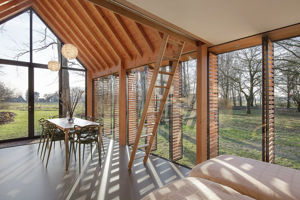 The house's ceiling was hewn from Douglas fir, which gives off a warm glow. The rafters were designed to emulate the look of strong ceiling beams. Tagged: Dining Room, Table, Chair, and Pendant Lighting.  Photo 3 of 9 in This Light-Filled Cabin in the Netherlands Is Completely Made by Hand from Utrecht Cabin