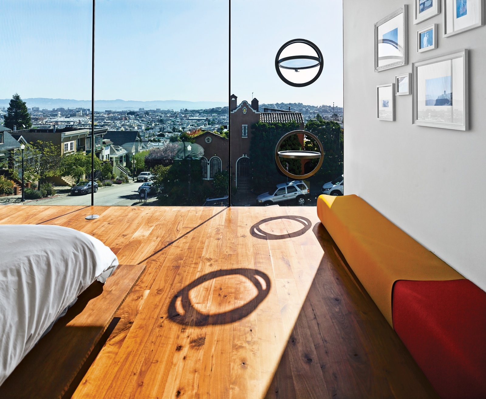 The LC4 lounge is by Le Corbusier, Charlotte Perriand, and Pierre Jeanneret for Cassina. Operable porthole windows on the east facade offer ventilation.  Photo 11 of 17 in Striking Slatted Wood and Glass Home in San Francisco