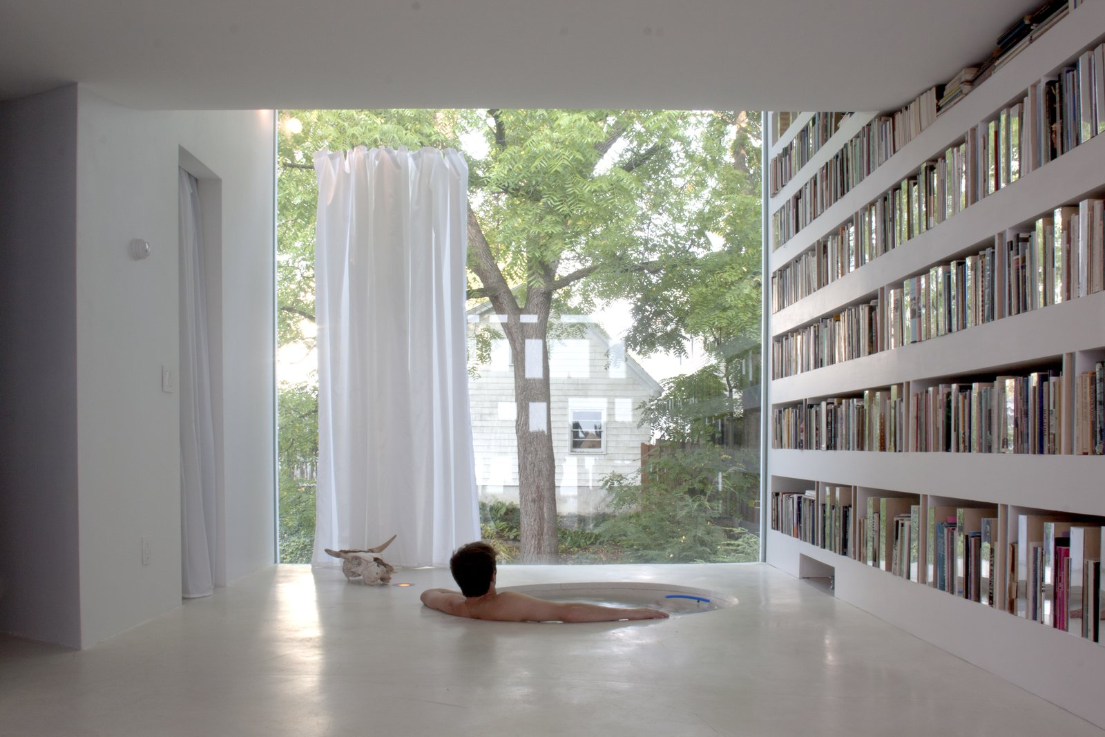 The studio's second floor serves as a library. The sunken bathtub offers interrupted sightlines across the space and out into the backyard. The tub, like the library's floor, is made of concrete. Tagged: Bath Room and Soaking Tub.  Read by DAVE MORIN from This Glowing Library Addition is Every Writer's Dream Escape