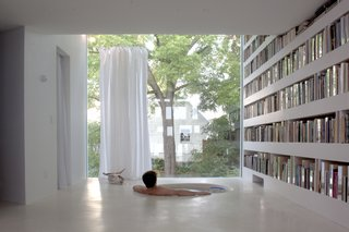 12 Functional Modern Home Libraries - Photo 1 of 12 - This studio replaced a single-story garage, which was demolished. Its ground level still serves as a carport, but the upper levels now house a library and reading room. The studio's second floor serves as a library. The sunken bathtub offers interrupted sight lines across the space and out into the backyard. The tub, like the library's floor, is made of concrete.
