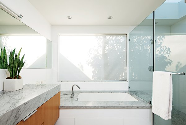 The minimalist bathroom boasts Cararra marble surfaces, Hansgrohe faucets and shower fixtures, and a skylight by Velux.