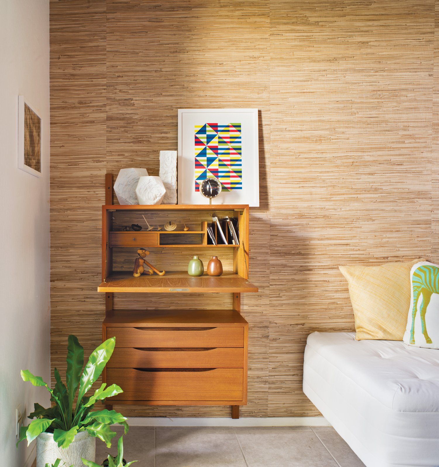 """A Good Reed  The most changed area of the home is the small guest room–office, where Neely, who works from home, removed the closet doors and added a grass-cloth wall treatment to distinguish it from the rest of the house's decor. """"Many of the Eichlers originally had grass cloth as a covering on the sliding closet doors,"""" he says. """"The guest room–office is the only other room that can be seen from the public areas across the atrium, and I wanted this wall to add visual interest."""" Tagged: Bedroom, Shelves, and Bed.  Bedrooms by Dwell from Modern Furniture Fit for a Classic Eichler"""