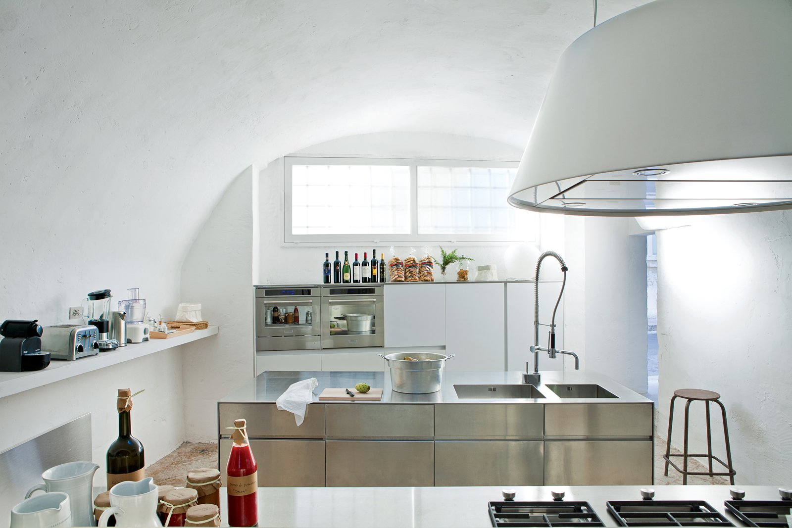In the minmalist kitchen: sleek steel cabinet systems and the Kono range hood from Elmar. Tagged: Kitchen, Metal Counter, Metal Cabinet, Drop In Sink, Range Hood, Wall Oven, Open Cabinet, Table Lighting, and Range.  Kitchen by Lara Deam from Modern Meets Ancient in a Renovated Italian Vacation Home