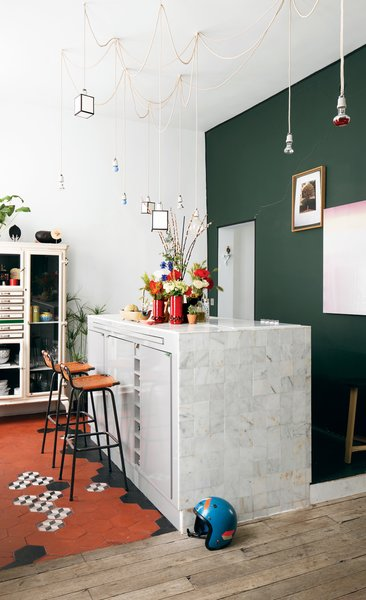 Aumas designed the kitchen island, which is covered in marble tiles from Carrelages du Marais—the geometric floor tiles are from the same place—and strung the matrix of lights up above it. The barstools by Charlotte Perriand were discovered in a vintage store in Antwerp, Belgium. The green wall is covered in paint from Emery & Cie. Tagged: Kitchen and Marble Counter.  Colorful Intentions by Meg Dwyer from A Furniture Collector's Renovated Flat in Paris