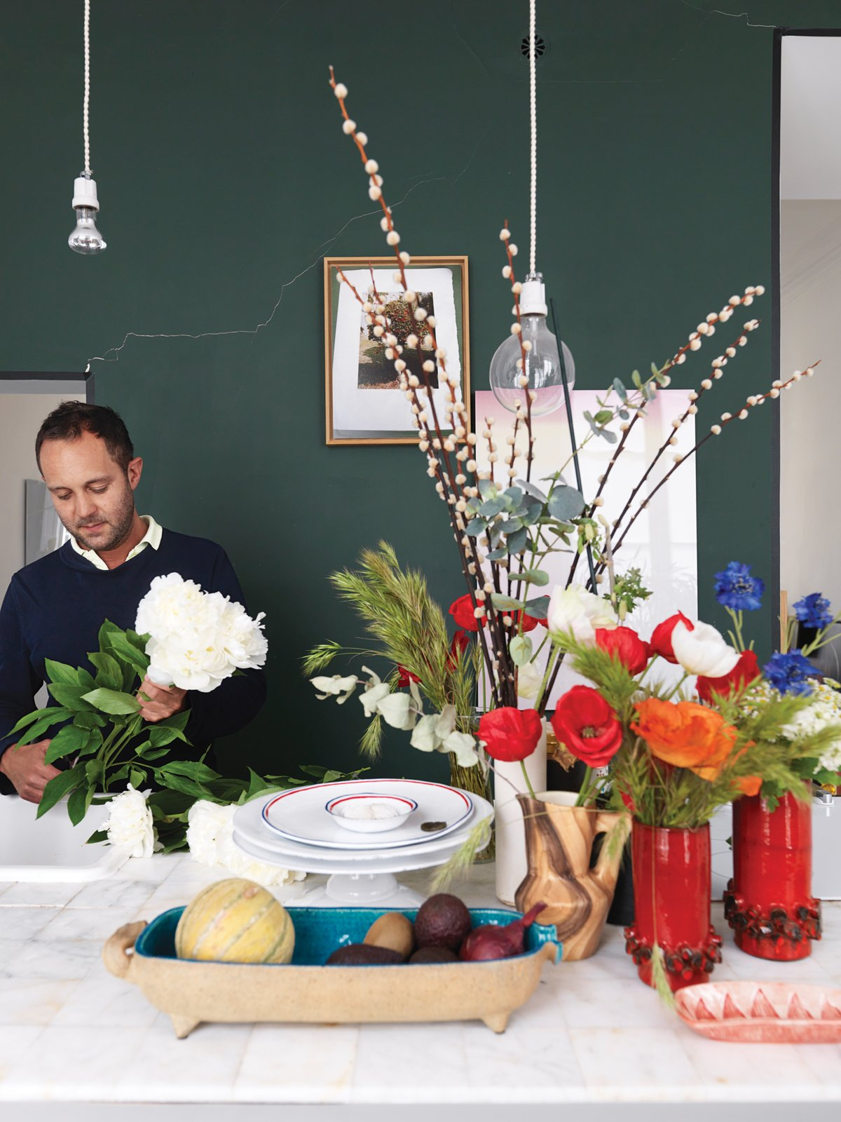 Ever the arranger, Aumas makes another vignette in the kitchen amid vintage vases and bowls. Tagged: Kitchen and Pendant Lighting.  Photo 6 of 12 in A Furniture Collector's Renovated Flat in Paris