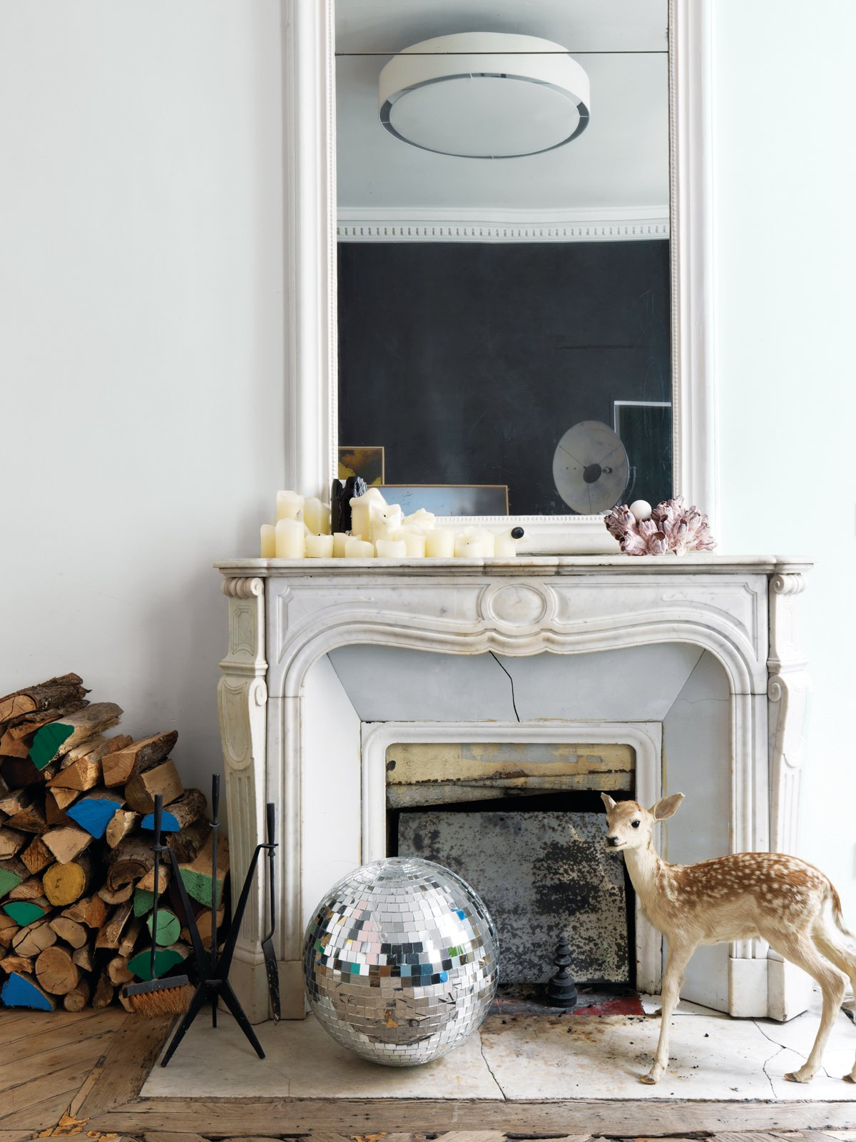 In another one of Aumas' vignettes, he pairs a stuffed fawn from the Parisian store Design et Nature with a disco ball he used in a window display. Tagged: Living Room and Standard Layout Fireplace.  97+ Modern Fireplace Ideas by Dwell from A Furniture Collector's Renovated Flat in Paris