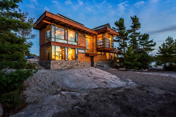 Beside the Georgian Bay in Ontario, architect and partner at Toronto's CORE Architects Charles Gane built a 2,100-square-foot getaway for himself that combines urban building practices with rugged self-sufficiency. The aluminum window system and flat roof are common characteristics of Toronto's high-rises, while the cedar shingles belong to cottage vernacular. Photo  of Monument Channel Cottage modern home