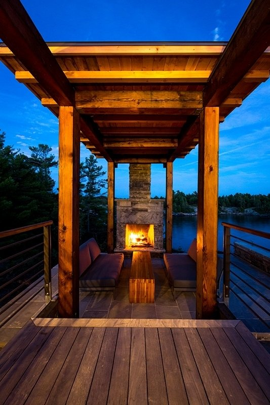 A covered fireplace and sitting area anchor the deck, which overlooks the water. Monument Channel Cottage by Allie Weiss