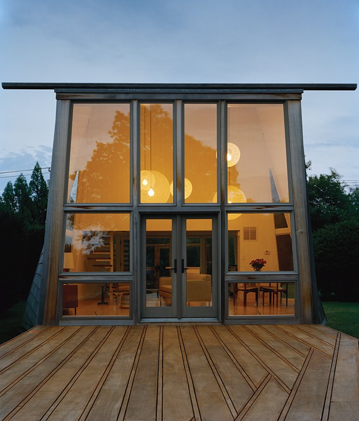The historically protected property that Christine and James Boyle purchased on Long Island came with two existing shingled structures designed by modernist architect Andrew Geller in 1963. Bates Masi recast what was originally the primary residence as a guest cottage.  Photo 3 of 9 in Modern Wood-Lined Family Home in the Hamptons