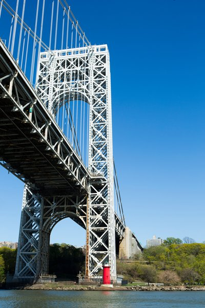 The George Washington Bridge towers over the Little Red Lighthouse. The lighthouse was popularized by a 1942 children's book and in 1951, public outcry prevented its dismantling. It is listed on the National Register of Historic Places.